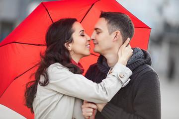 Couple in love under red umbrella.