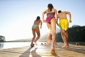Family running on wooden dock at lake