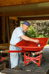Senior  paint  a wheelbarrow in red