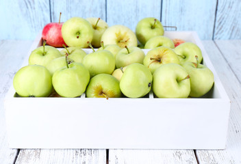Ripe apples in box on wooden table close-up