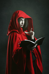 Dark red hooded witch reading a book