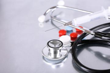 Stethoscope, syringe, pills