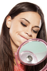 young beautiful woman makes a face in the mirror