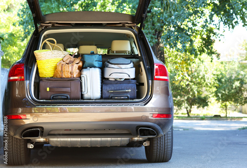 Suitcases and bags in trunk of car ready to depart for holidays - 71617888