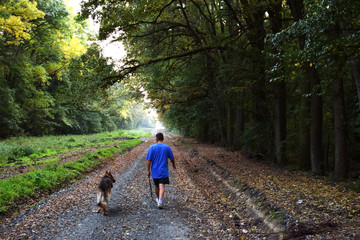 Man walking in the forest with dog