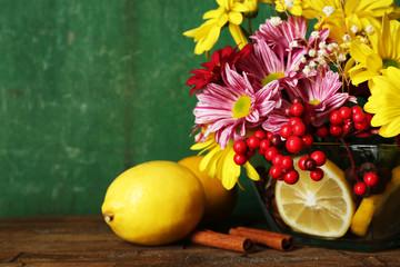 Beautiful chrysanthemum and lemons on wooden background