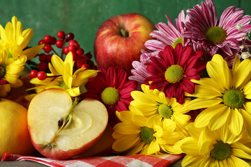 Composition with chrysanthemum and fruits on wooden background