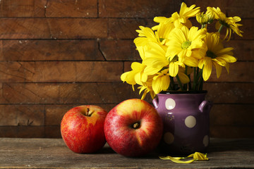 Beautiful chrysanthemum in water-can and apples