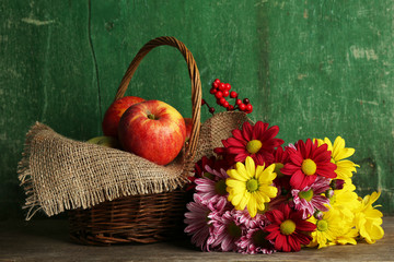 Beautiful chrysanthemum with apples in basket