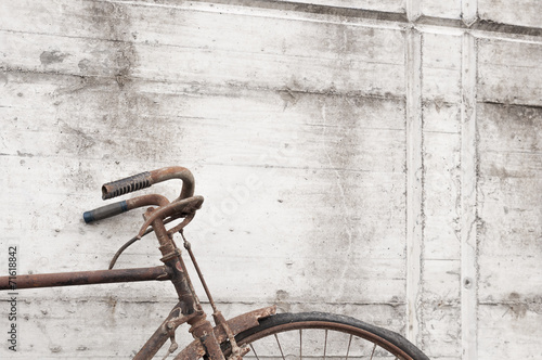 Bicycle Antique or retro oxidized bicycle outside on a concrete wall