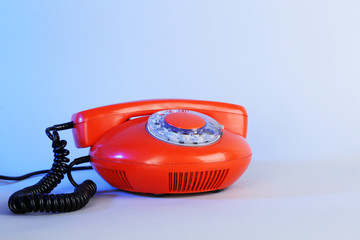 Old red disk phone on blue background