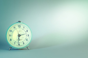 Old alarm clock on blue background