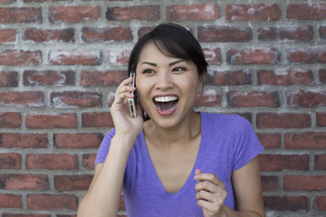 A young woman is overjoyed as she is talking on her phone
