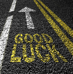 good luck and arrow on the asphalt road