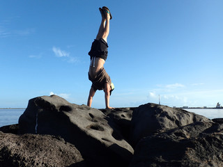 Man Handstands on rock jetty in Kahului Harbor
