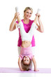 woman and kid daughter doing yoga exercise at mat