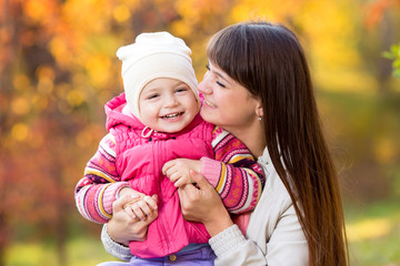 playful beautiful mother and kid girl outdoors in fall