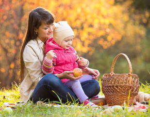 kid and mother sit with apples basket outdoors in autumnal park