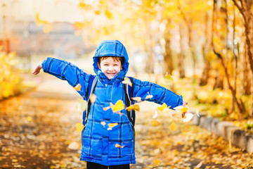 Happy little boy throws the autumn leaves in the air.