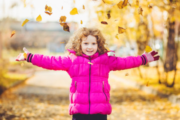 Happy little girl throws the autumn leaves in the air.