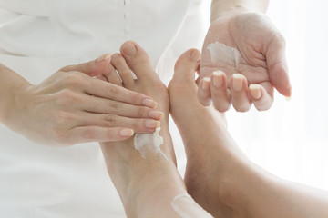 Esthetician to apply the cream to the feet of women
