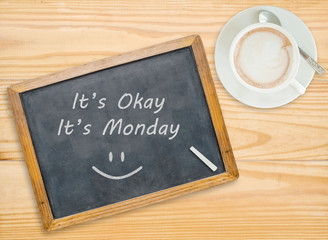 It's Okay ,It's Monday on chalkboard with coffee cup