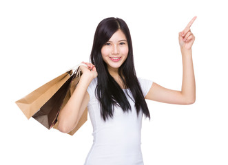 Happy woman hold with shopping bag and finger point up