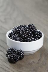 ripe blackberries in white bowl on old oak table