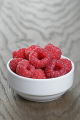 ripe raspberries in white bowl on old oak table