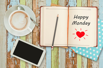 """Happy Monday""on notebook with smart phone and coffee cup"