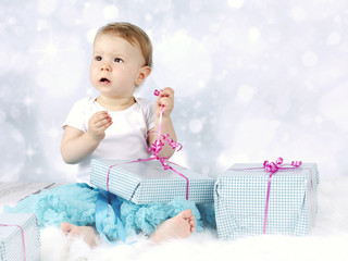 Little baby girl unwrapping christmas presents
