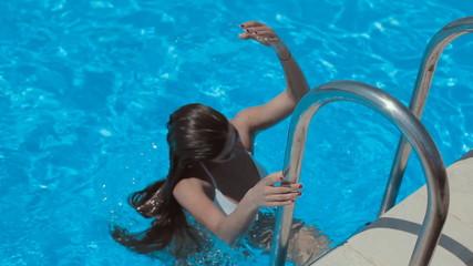 Sexy girl in a white bikini swimming in the pool