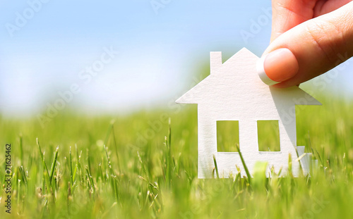 Paper house in green grass over blue sky. Mortgage concept - 71625462