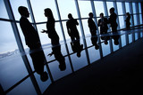 Silhouettes of business people interacting in board room