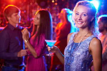 Beautiful girl posing with cocktail in nightclub