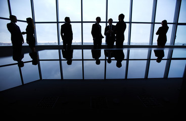 Silhouettes of people standing against a panoramic window