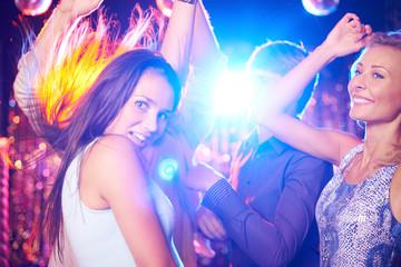 Energetic young people dancing in night club