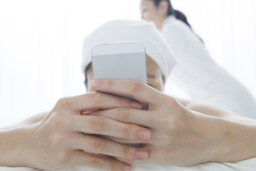 Who are looking at the mobile phone while getting a massage