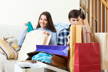 Happy friends with clothes and shopping bags