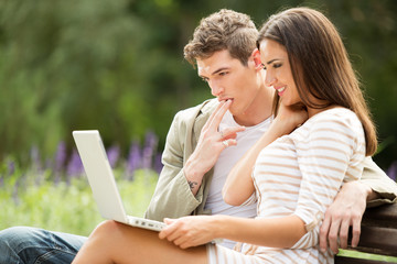 Young Couple Using Laptop At Park