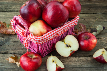 red apples in a basket on wooden background