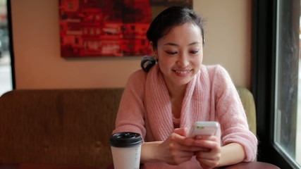 Young Asian woman texting cellphone in a cafe