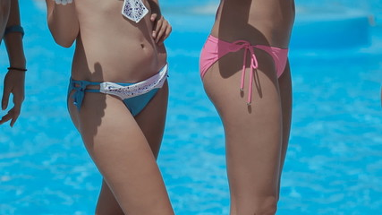 Beautiful models in bikini having fun near the pool