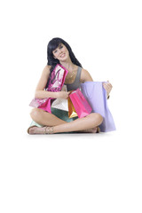 young attractive girl sitting surrounded by shopping parcels