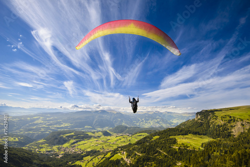 Paraglider flying over mountains - 71629481