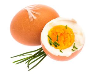 Ganzes und halbes gekochtes Ei mit Schnittlauch vor weißem Hint