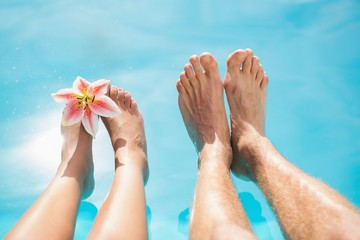 Couple feet against swimming pool on a sunny day