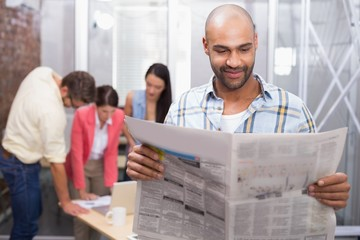Smiling man reading the newspaper