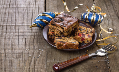 Christmas fruit cake over rustic wooden background