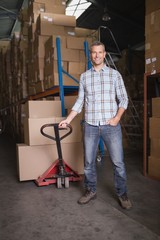 Worker with trolley of boxes in warehouse